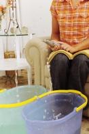 eaking roof or pipe burst: woman calling insurance or plumber