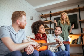 Group of friends having fun playing a guitar and singing